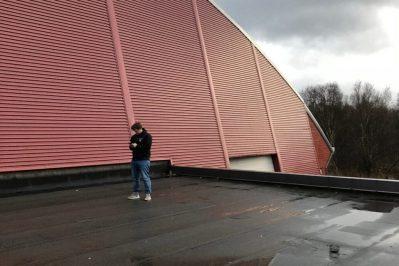 En person som står på taket for Rehabilitering Vesterålshallen